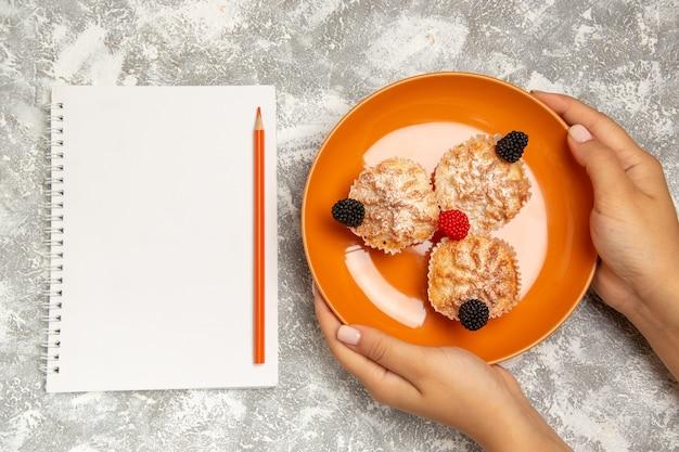 白い背景の上の砂糖粉とメモ帳でおいしい生地ケーキの上面図 無料写真
