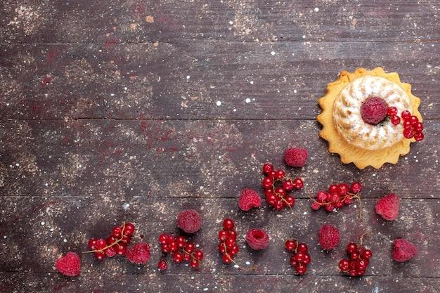 茶色の素朴な背景に沿ってラズベリークランベリーと一緒に砂糖粉とおいしい小さなケーキの上面図ベリーフルーツケーキビスケットの色 無料写真