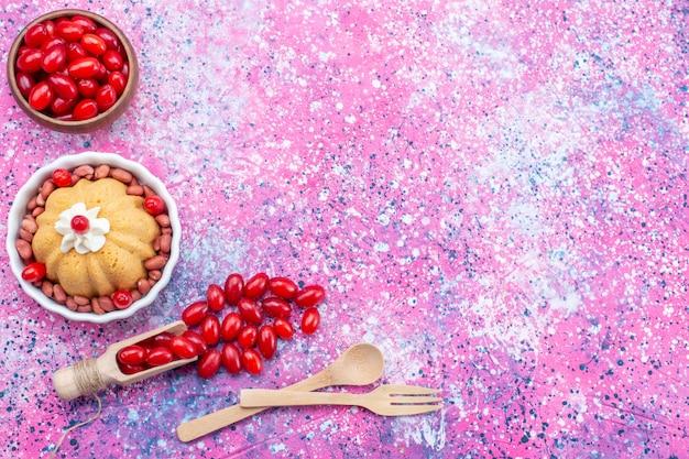 Вид сверху вкусный простой торт со сливками и свежим арахисом вместе со свежим красным кизилом на ярком светлом настольном пироге, бисквитном сладком орехе и ягодах Бесплатные Фотографии