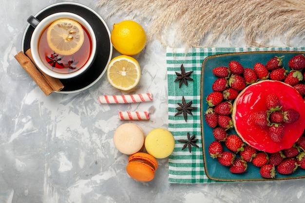 Вид сверху вкусный клубничный торт со свежей клубникой, чашкой чая и макаронами на белом столе Бесплатные Фотографии