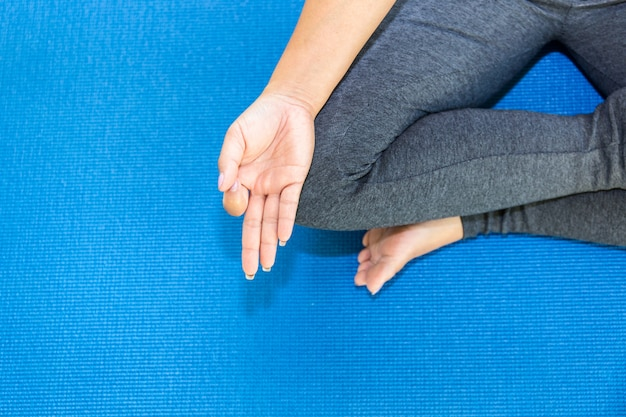 Top views attractive young woman working out at home, doing yoga exercise on blue mat Premium Photo