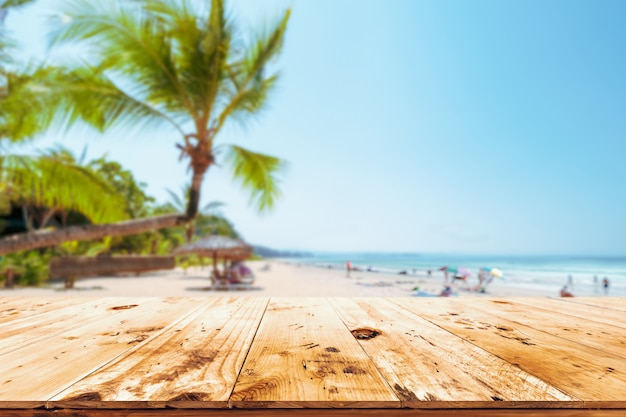 Top of wood table with seascape, palm tree, calm sea and sky at tropical beach Premium Photo