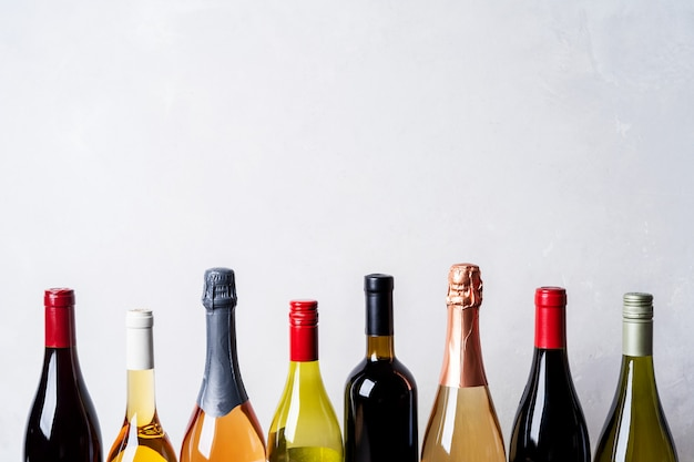 Tops from different kinds new bottles of champagne, white, red wine on light background Premium Photo