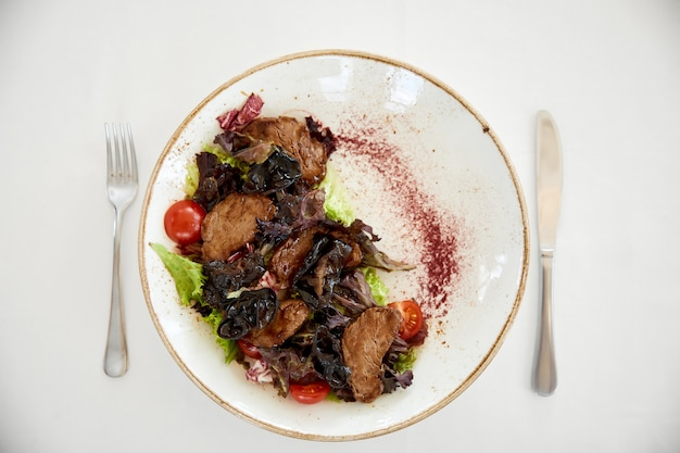 Topview of served beef salad with a cherry tomatos and lettuce on the white table Free Photo