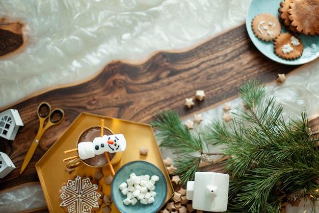 クリスマスの装飾が施されたトップビューテーブル。砂糖釉で飾られたマシュマロの雪だるま。雪片の形のジンジャーブレッドクッキー。 Premium写真