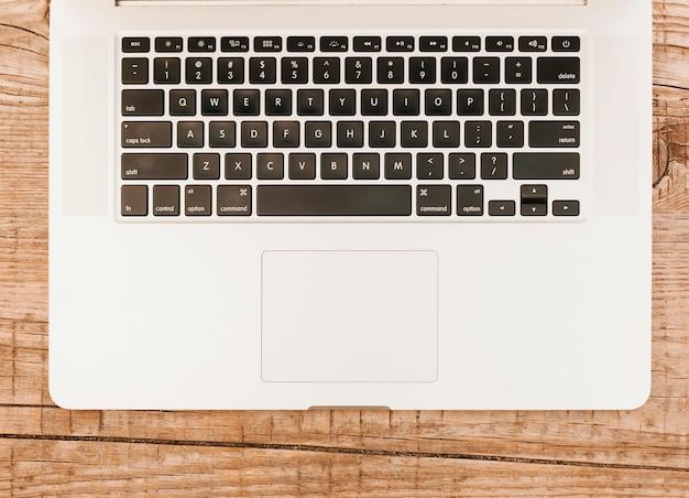 Topviewノートパソコンのキーボードの木製の背景 無料写真