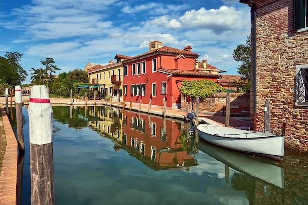 Torcello, venice. colorful houses on torcello island, canal and boats. summer, italy Premium Photo