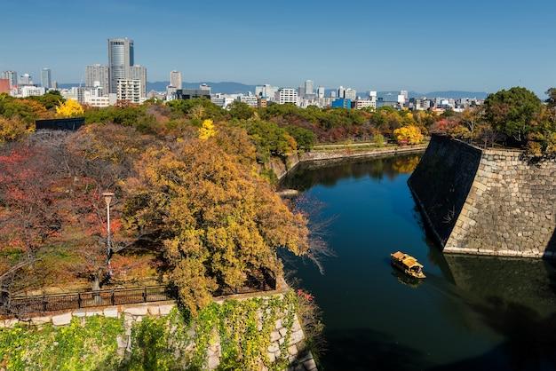 秋の木々を持つ大阪城のトーリストボート Premium写真