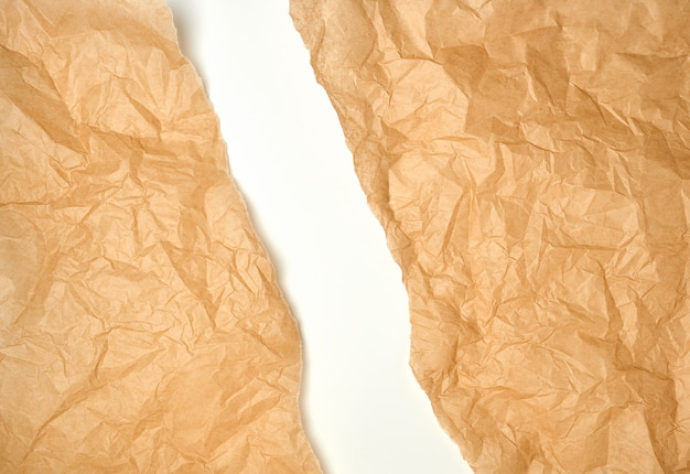 Torn crumpled brown parchment paper, white background Premium Photo