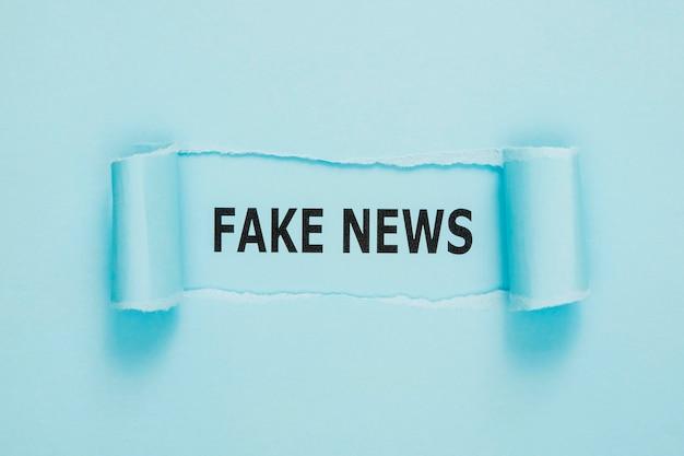Strappato giornale di notizie false sulla parete blu Foto Gratuite