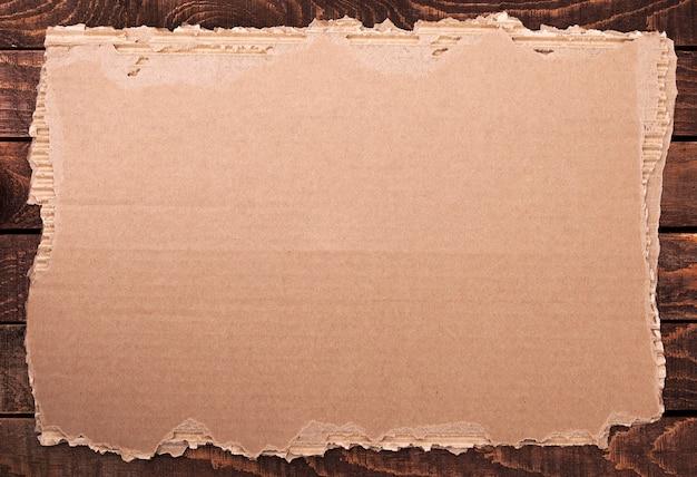 Рваная бумага. сорванный картон на деревянной текстуре. Premium Фотографии