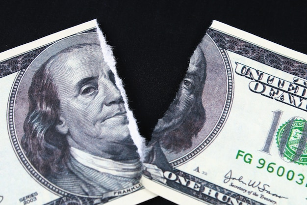 Torn ripped devalued one hundred dollar bank note. collapse of dollar. devaluation. falling currency Premium Photo