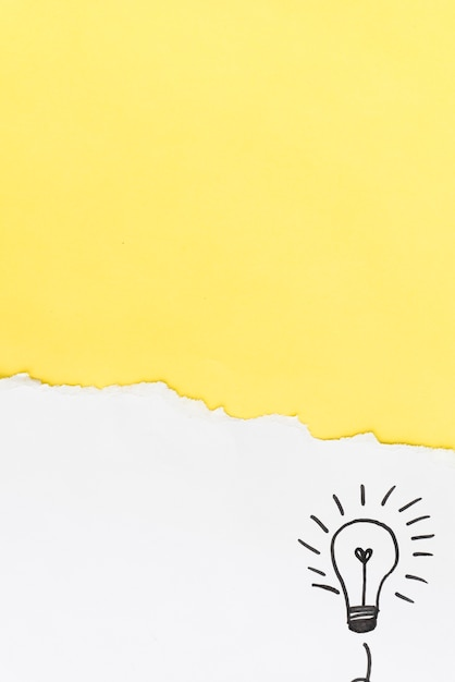 Torn yellow paper with hand drawn light bulb on white background Free Photo