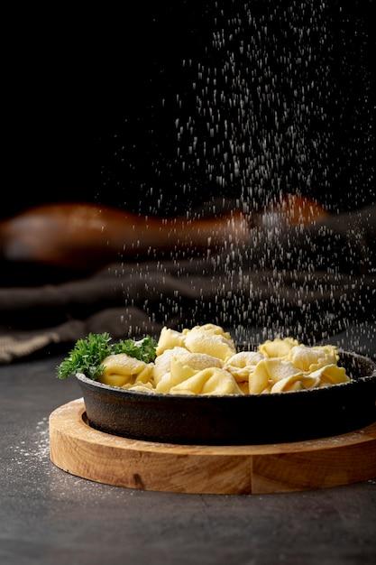 Tortellini in dark metallic plate on a wooden stand Free Photo