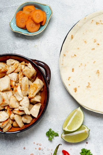 Tortilla and chicken dish near sliced carrots and lime Free Photo