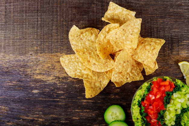 Tortilla chips, avocado dip, tomato and cucumber Premium Photo