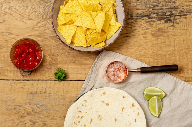 Tortilla and nachos near tomatoes, pink salt and sliced lime Free Photo