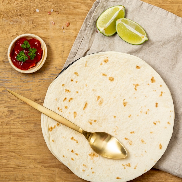 Tortilla with spoon, tomato sauce and sliced lime on table Free Photo