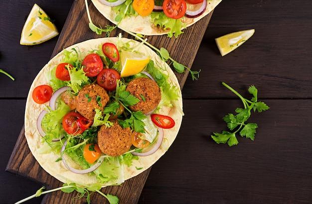Tortilla wrap with falafel and fresh salad. vegan tacos. vegetarian healthy food. top view Premium Photo