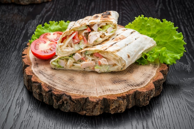 Tortilla wraps with grilled chicken or vegetarian tarteel of fresh vegetables on a wooden background Premium Photo