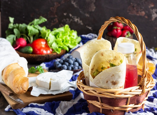 Tortilla wraps with roasted chicken and vegetables, juices, vegetables and berries, baguette and cheese. Premium Photo