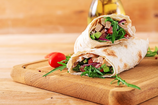 Tortillas wraps with chicken and vegetables on  wooden background. chicken burrito. healthy food. Premium Photo