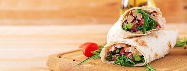 Tortillas wraps with chicken and vegetables on  wooden background. Premium Photo