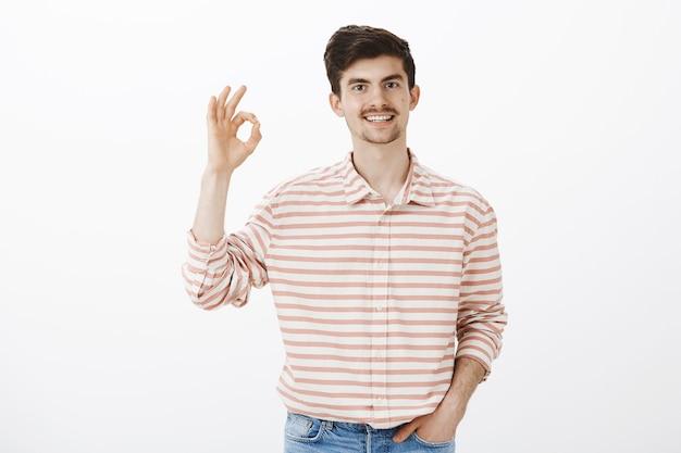 完全にあなたに同意します。ひげと口ひげを持つ穏やかな幸せな白人男の屋内ショット、大丈夫なジェスチャーで手を上げる、コンセプトを承認、思考のアイデアは素晴らしい、灰色の壁の上に立って 無料写真