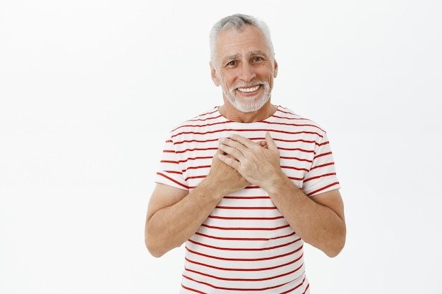 Touched and flattered senior grandfather with beard looking happy and grateful Free Photo