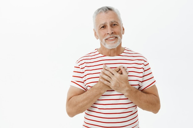 Touched and happy, flattered senior man holding hands on heart and smiling Free Photo