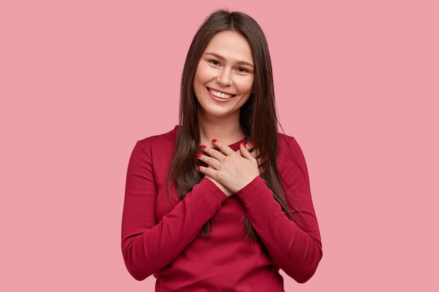 Touched positive woman with pleased expression keeps hands on chest, feels gratitude, impressed by good words of gratitude, isolated over pink background. people Free Photo
