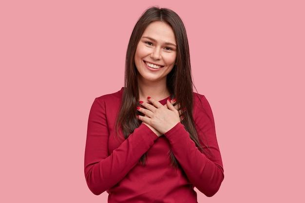 Прикосновенная позитивная женщина с довольным выражением лица держит руки на груди, чувствует благодарность, впечатленная добрыми словами благодарности, изолированными на розовом фоне. люди Бесплатные Фотографии