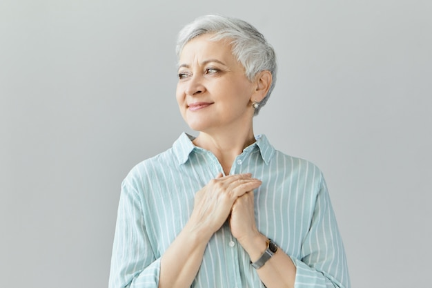 Toccata grata affascinante femmina caucasica in pensione di mezza età che guarda lontano con un gentile sorriso grato, mostrando gratitudine e apprezzamento per amore, sostegno, auguri cordiali, sostegno e cura Foto Gratuite