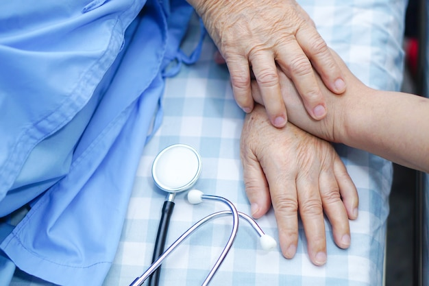 Touching hand asian senior or elderly old lady patient with love, care, encourage and empa Premium Photo