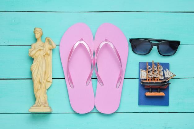 Концепция туризма. фон путешественника. путешествуйте по миру в стиле flat lay. туристические аксессуары, сувениры на синем деревянном фоне. Premium Фотографии