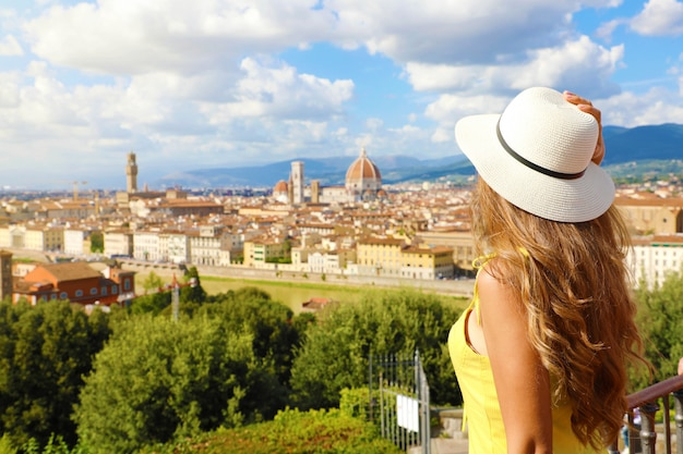 Туризм в италии. вид сзади молодой женщины, наслаждаясь панорамным видом на город флоренция, тоскана, италия. Premium Фотографии