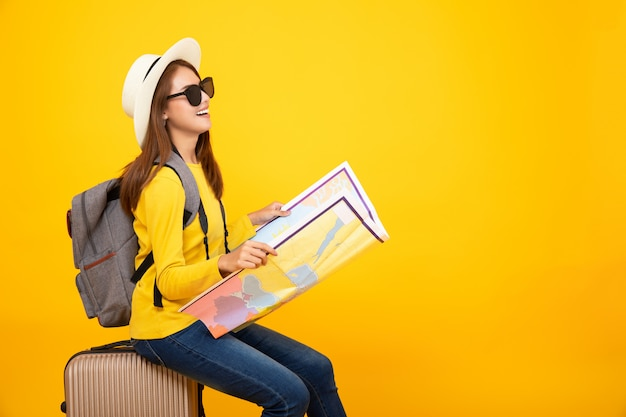 Tourist asian woman look at the map with bag on the yellow background Premium Photo