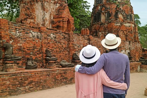 タイのアユタヤ歴史公園で頭のない仏像のグループを眺めながら観光客のカップル Premium写真