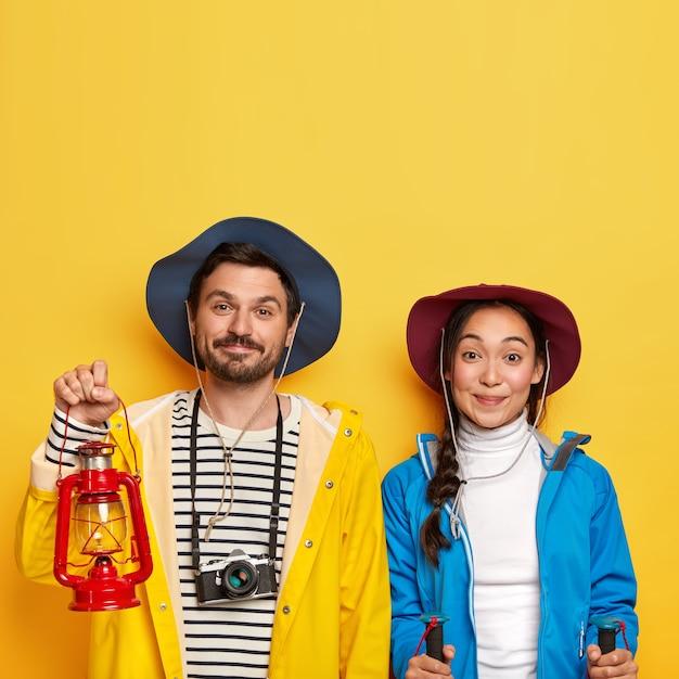 Le coppie di turisti fanno una spedizione insieme, fanno un'escursione in montagna, usano bastoncini da trekking, fotocamera retrò per fare foto, vestiti con abbigliamento sportivo, cappelli, isolati su muro giallo Foto Gratuite