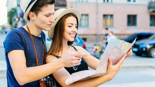 Tourist couple looking at map Free Photo