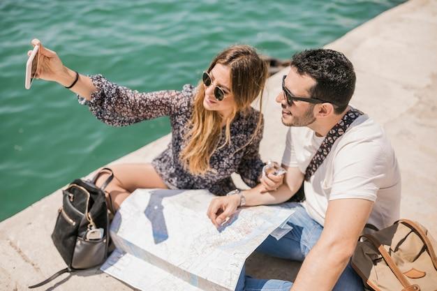 Туристическая пара, сидя на пристани, говорить автопортрет на мобильный телефон Бесплатные Фотографии