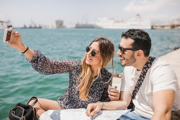 Tourist couple sitting with map on jetty taking selfie on cell phone Free Photo