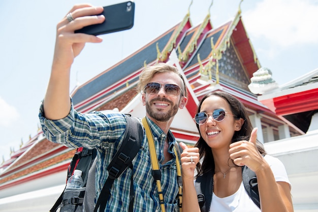 Tourist couple taking selfie at thai temple on vacations in thailand Premium Photo