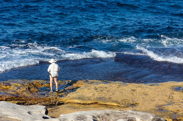 Tourist in hat standing with fishing rod in hand Premium Photo