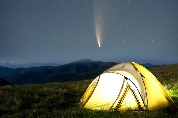 Tourist hikers tent in mountains at night with stars and neowise comet with light tail in dark night Premium Photo