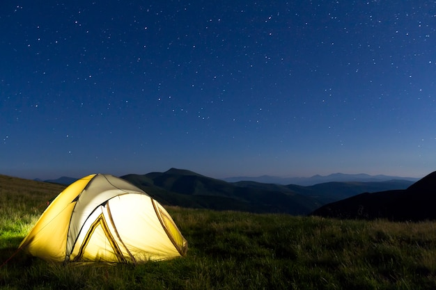 Tourist hikers tent in mountains at night with stars in the sky Premium Photo