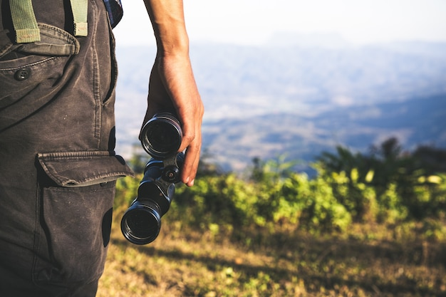 Tourist is holding through binoculars on sunny cloudy sky from mountain top. Free Photo