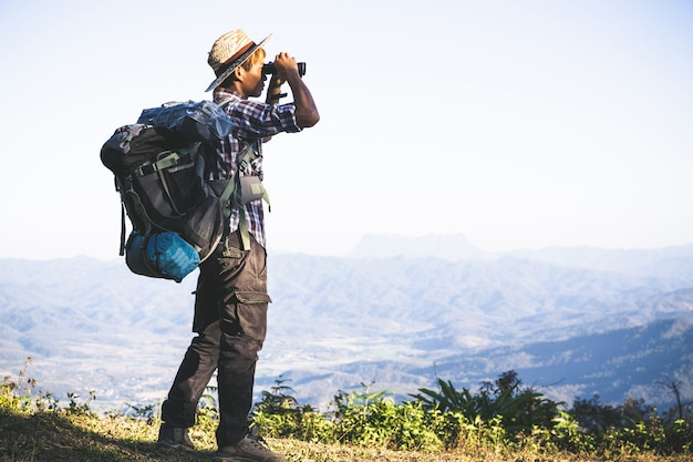 Tourist is watching through binoculars on sunny cloudy sky from mountain top. Free Photo