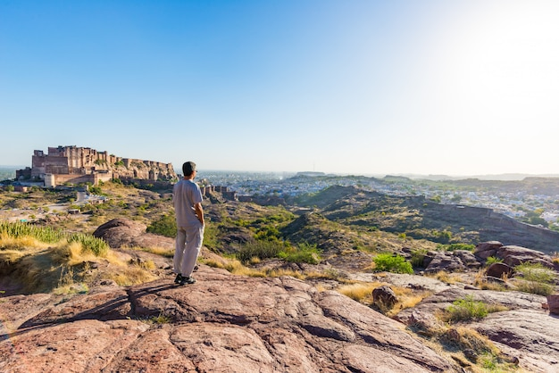 Tourist standing on rock and looking at expansive view of jodhpur fort from above, perched on top dominating the blue town. travel destination in rajasthan, india. Premium Photo