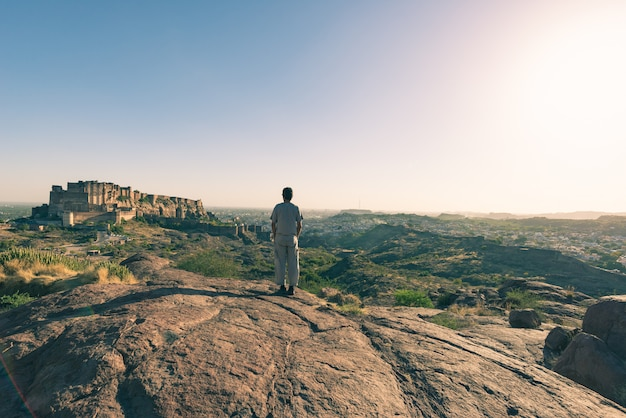 Tourist standing on rock and looking at expansive view of jodhpur fort from above Premium Photo